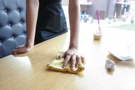 Waitress cleaning the table in coffee shop
