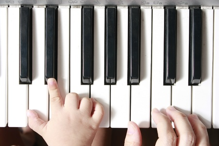 A photo of the hand of a child and a teacher or a parent on a keyboardpiano implicating that the adult is teaching the child