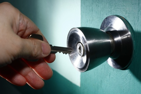 A photo of a hand holding a key and about to open a door Stock Photo - 11814360