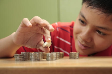 A photo of a boy stacking a pile of coins photo