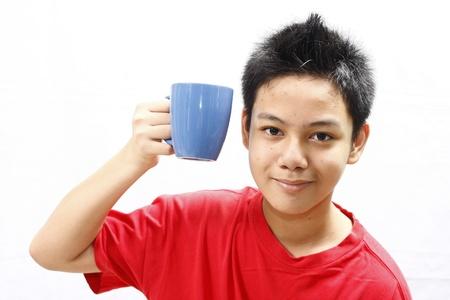 839daf68bba Boy Holding a Mug close to his face Stock Photo