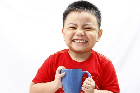 Little Boy Holding A Mug and Smiling