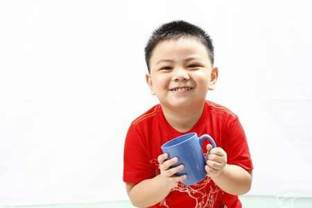 Little Boy Holding A Mug and Smiling photo