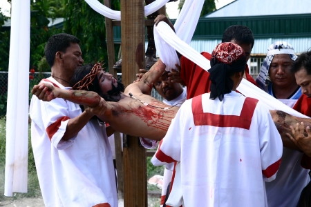 enact: Cainta, Rizal, Philippines. March 29, 2013. An actor in the role of Jesus is brought down from a cross in a re-enactment of Christs crucifixion and death. A tradition in the Philippines called Senakulo is held yearly every Holy Week.