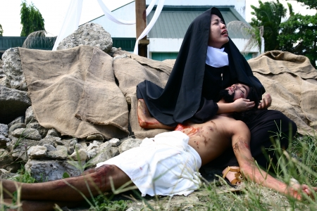 reenact: Cainta, Rizal, Philippines. March 29, 2013. Actors playing the roles of Mama Mary and Jesus Christ re-enact the death and crucifixion of Christ.  A tradition in the Philippines called Senakulo is held yearly every Holy Week.