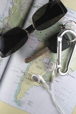 ear buds: A photo of travel paraphernalia such as key, ear buds, sunglasses and a map