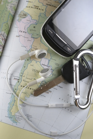 ear buds: A photo of travel paraphernalia such as key, ear buds, cellphone and a map