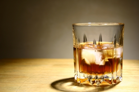 rhum: Alcoholic Drink in a Glass with Ice  A photo of an alcoholic drink or liquor with ice in a glass and on a table
