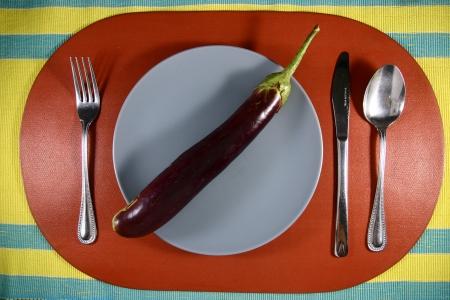 egg plant: Una planta de huevo en un plato Una foto de una planta de huevo en una placa de fijaci�n con utensilios