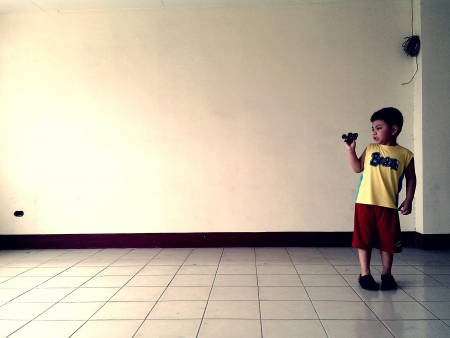 tile: an asian boy plays with his toy car in an empty room Stock Photo