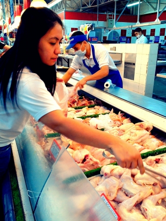a customer selects a piece of fresh chicken to buy at a supermarket