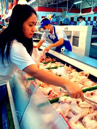 selects: un cliente sceglie un pezzo di pollo fresco per comprare in un supermercato