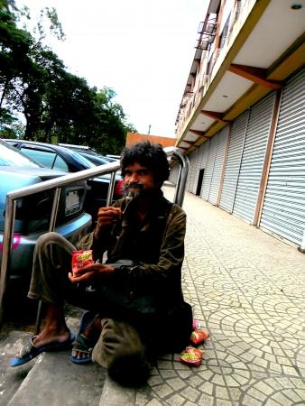 Beggar sitting at a sidewalk as he eats Reklamní fotografie