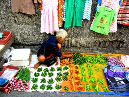 clothes: Old lady vendor selling vegetable and clothes in a market in cainta rizal philippines asia Stock Photo