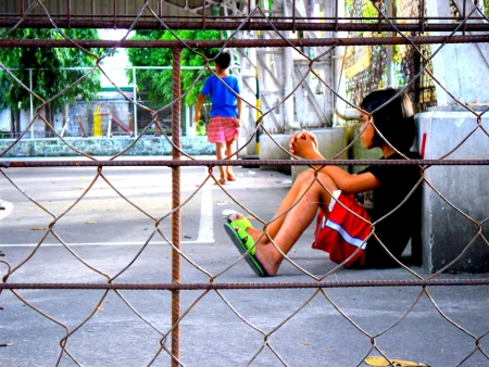 wire: Young asian girl rests and sit down inside a closed basketball court in a park