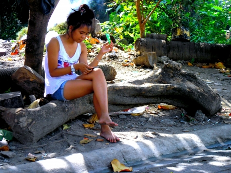 tree works: A girl works on her smartphone under the shade of a tree