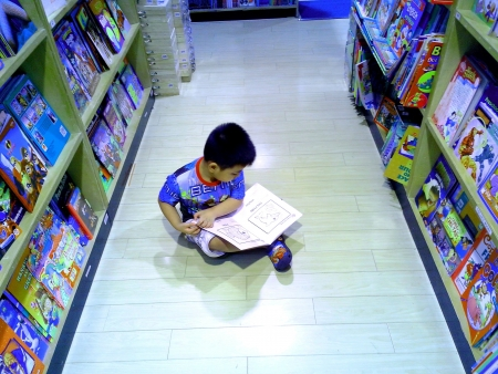 Little asian boy reading childrens books in a bookstore