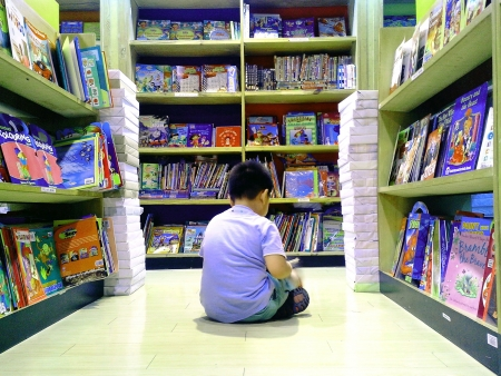 Little boy reads childrens books inside a bookstore