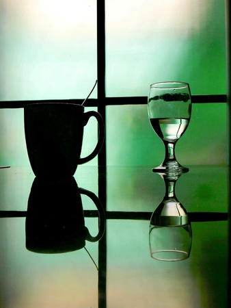 reflective: Water in a water goblet and coffee mug on a reflective table