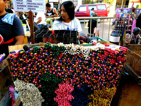 beside: Street vendor in quiapo manila philippines selling candles beside a church