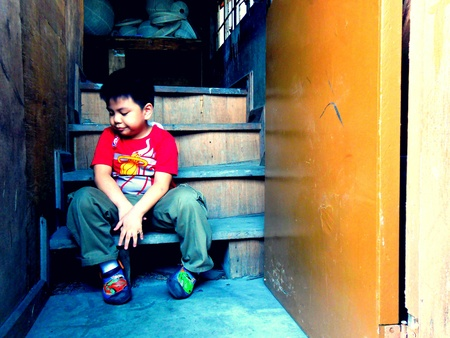 doorstep: Young asian boy sitting on the steps of a staircase by the doorstep