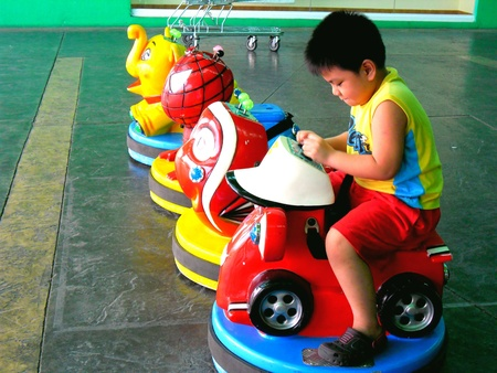kiddie: Asian child playing with kiddie rides