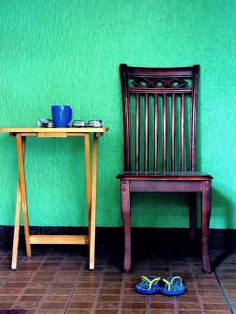 back: Wooden chair, a pair of flip flops, coffee mug, eyeglasses and newspaper