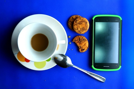 silver: Finished coffee in a cup and saucer with cookies, a teaspoon and a cellphone