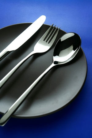silver: Spoon, fork, knife and ceramic dinner plate Stock Photo