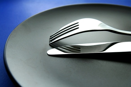 silver: Fork, knife and ceramic dinner plate Stock Photo