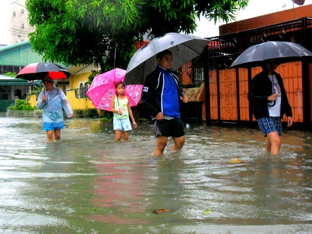 Residents of cainta, rizal, philippines walk in flood waters caused by typhoon mario fung wong