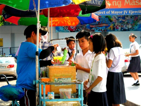 Young asian students buying food from a street vendor