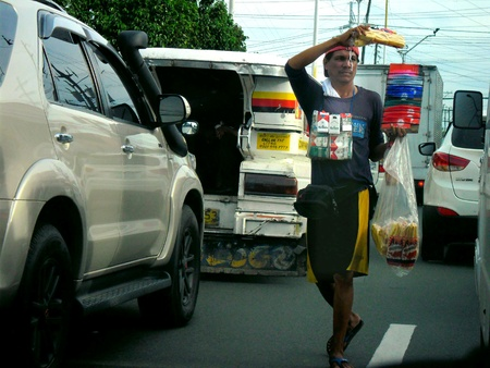Asian man selling food and cigarette in the streets of manila