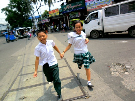 Young asian students run to cross a street