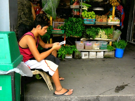 vend: Man sits in front of his fruits and vegetable store in a market Stock Photo