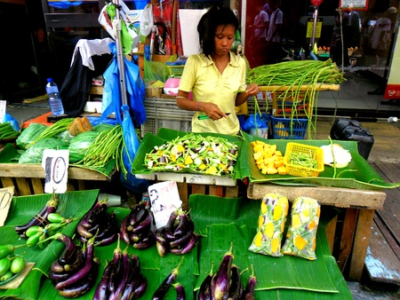 vend: Asian lady selling vegetable in a market in quiapo, manila, philippines in asia