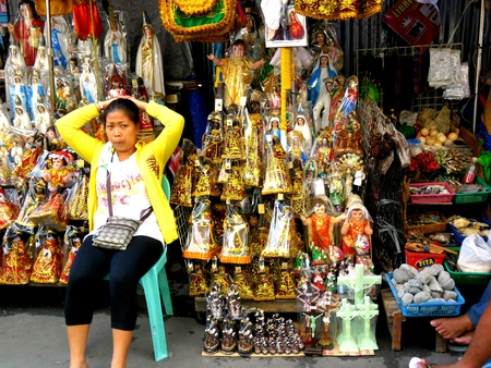 vend: Asian lady selling religious items in quiapo, manila, philippines in asia