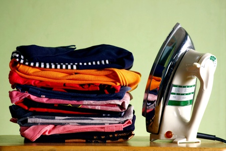 apparel: Folded shirts and an iron Stock Photo