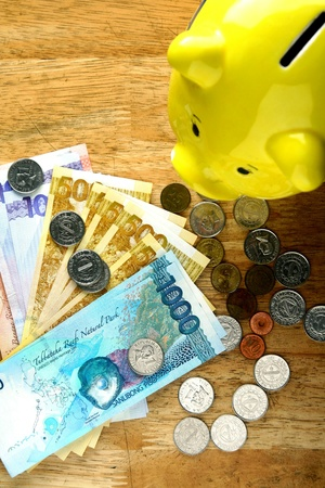 philippine: Money on a wooden table and a coin or piggy bank Stock Photo
