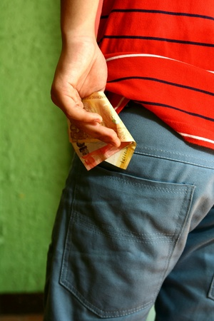 putting money in pocket: Person holding money in his hand and putting it into back pocket