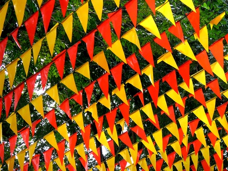 tree linked: Colorful triangle shaped flaglets hung as decoration for a feast celebration Stock Photo