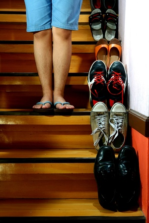 beside: Person standing beside Different shoes on a staircase