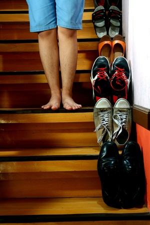 Person on barefeet standing beside Different shoes on a staircase Stock Photo