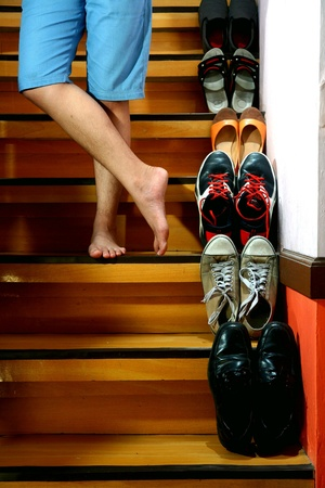beside: Person on barefeet and cross legged standing beside Different shoes on a staircase
