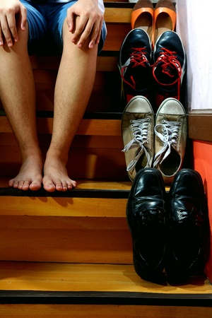Person on barefeet and sitting beside Different shoes on a staircase