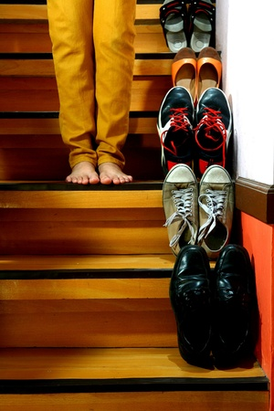 beside: Person on barefeet wearing long pants and standing beside Different shoes on a staircase