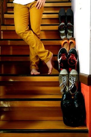 beside: Person on barefeet and wearing long pants and standing beside Different shoes on a staircase
