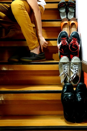 Person putting on shoes while sitting beside Different shoes on a staircase