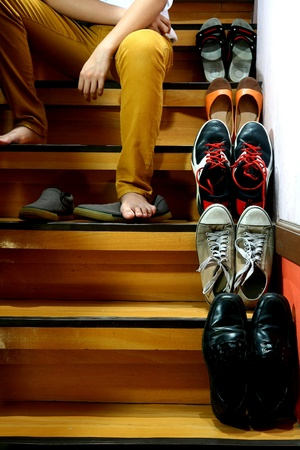 pants: Person putting on shoes while sitting beside Different shoes on a staircase