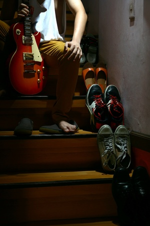 wear: Person with a guitar sitting beside Different shoes on a staircase